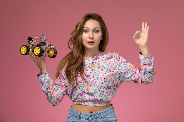 Vorderansicht junge schöne frau in blume entworfenes hemd und blaue jeans, die spielzeugauto halten, das auf dem rosa hintergrund aufwirft