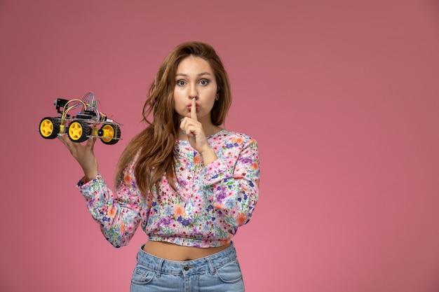 Vorderansicht junge schöne frau in blume entworfenes hemd und blaue jeans, die spielzeugauto halten, das schweigenzeichen auf rosa hintergrund zeigt