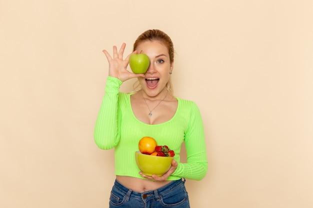 Vorderansicht junge schöne frau in grünem hemd, das platte mit früchten hält und grünen apfel auf der hellen cremefarbenen wandfruchtmodell-frauenpose hält