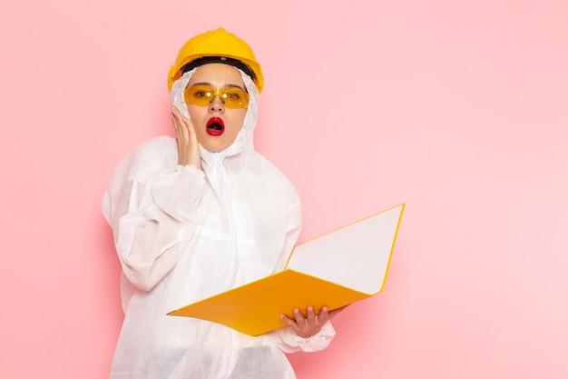 Vorderansicht junge schöne frau in speziellem weißen anzug, der schutzhelm hält, der gelbe dateien auf der rosa raumspezialanzug-mädchenfrau hält