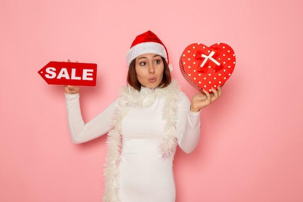 Vorderansicht junge weibliche holding verkauf schreiben und präsentieren auf rosa wand urlaub neujahr mode schnee weihnachten