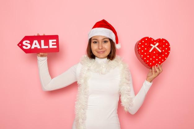 Vorderansicht junge weibliche holding verkauf schreiben und präsentieren auf rosa wandfarbe urlaub neujahr mode schnee weihnachten