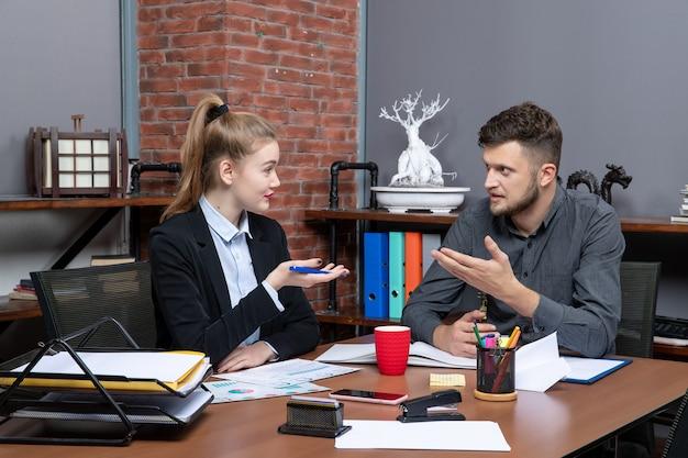 Vorderansicht junger beschäftigter büroangestellter, die ein wichtiges thema im büro diskutieren