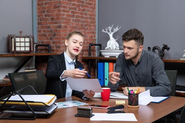 Vorderansicht junger beschäftigter büroangestellter, die ein wichtiges thema in dem dokument im büro diskutieren