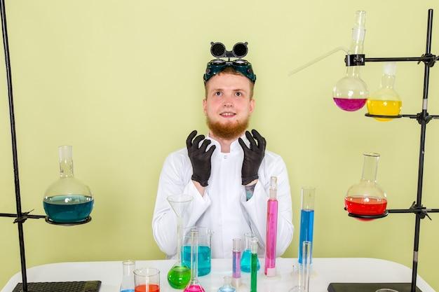 Vorderansicht junger chemiker denken über seltsame absichten nach