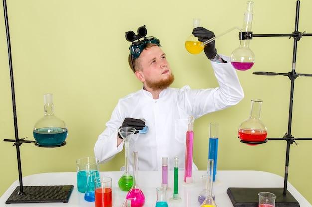 Vorderansicht junger chemiker, der über gelbe chemikalie in einem labor forscht