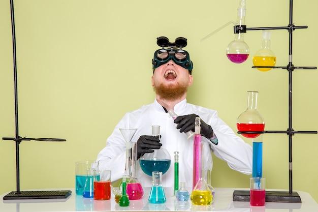 Vorderansicht junger chemiker, der über seine teufelsabsichten lacht
