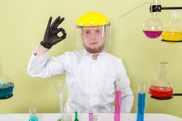 Vorderansicht junger chemiker mag seinen helm in einem labor