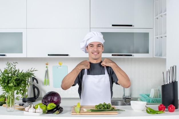Vorderansicht junger koch in uniform, der hinter dem tisch steht