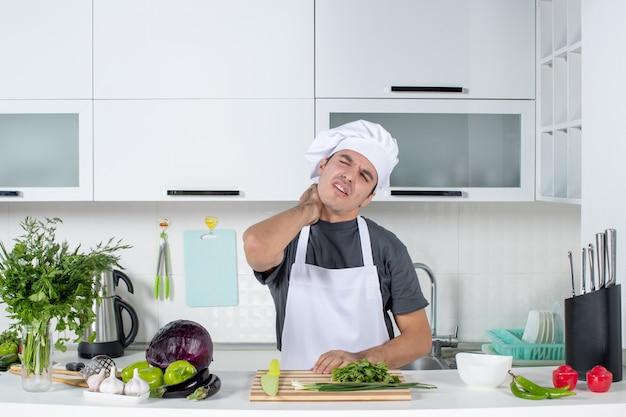 Vorderansicht junger koch in uniform, der seinen hals hält