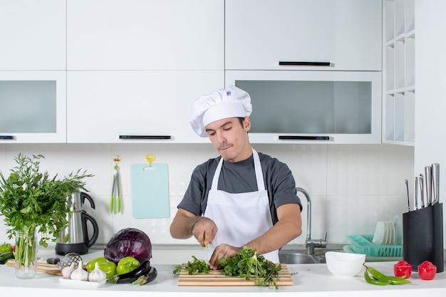 Vorderansicht junger koch in uniform hacken grüns auf schneidebrett