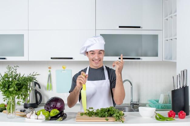 Vorderansicht junger koch in uniform mit messer, das auf die decke zeigt