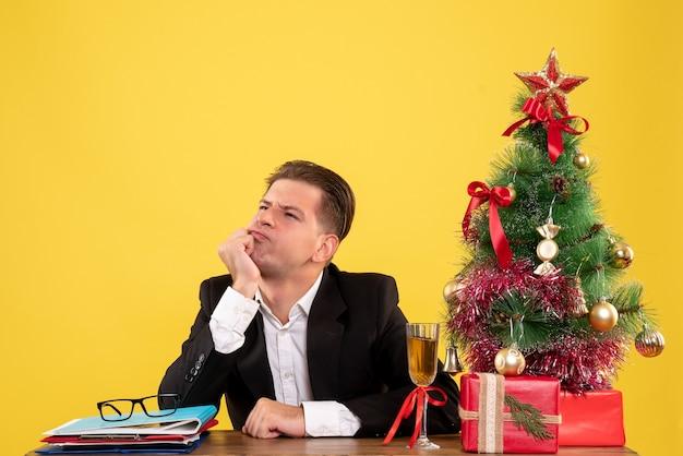 Vorderansicht junger männlicher arbeiter, der mit weihnachtsgeschenken und baum sitzt, der stressig denkt