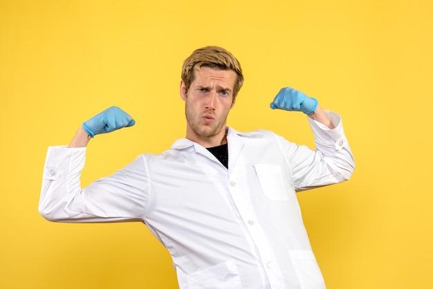 Vorderansicht junger männlicher arzt, der auf gelbem hintergrund menschliche covid medic pandemie biegt