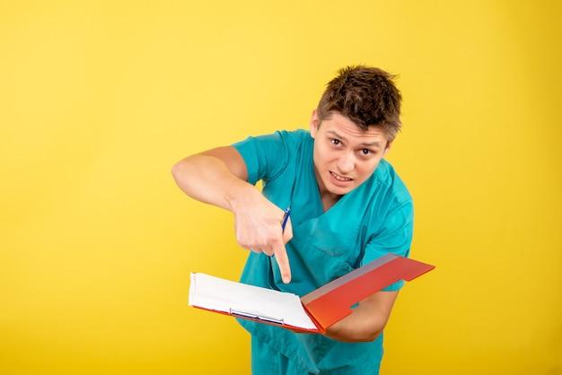 Vorderansicht junger männlicher arzt im medizinischen anzug mit notizen auf gelbem hintergrund
