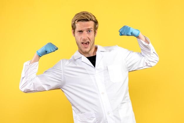 Vorderansicht junger männlicher arzt lächelnd und biegend auf gelbem hintergrund menschlicher covid medic
