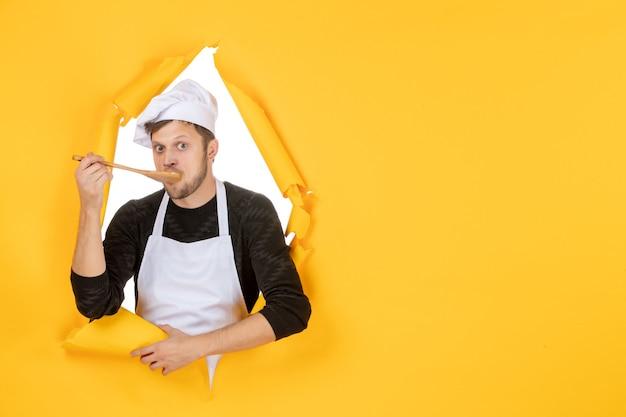 Vorderansicht junger männlicher koch in weißem umhang, der holzlöffel auf gelbem hintergrund schmeckt