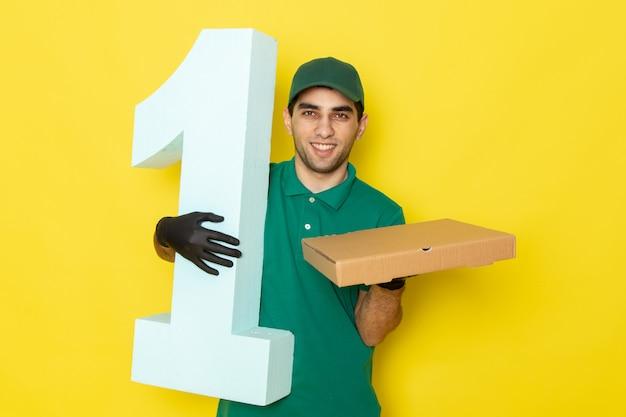 Vorderansicht junger männlicher kurier, der kasten und nummer eins hält, die auf gelb lächeln