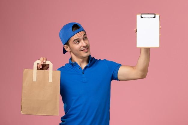 Vorderansicht junger männlicher kurier in blauer uniform und umhang mit lieferpaket und notizblock auf seinen händen an der rosa wand