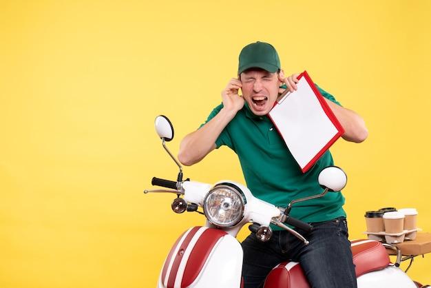 Vorderansicht junger männlicher kurier in grüner uniform mit aktennotiz auf gelb
