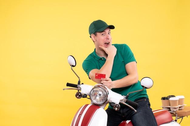 Vorderansicht junger männlicher kurier in grüner uniform mit bankkarte auf gelb