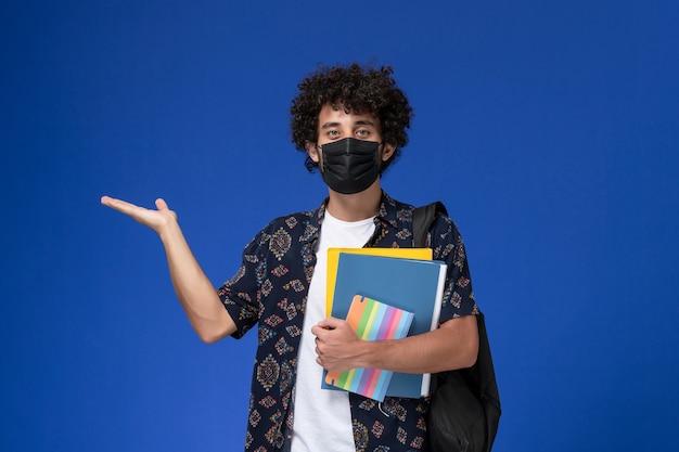 Vorderansicht junger männlicher student, der schwarze maske mit rucksack hält, der dateien und heft auf blauem hintergrund hält.