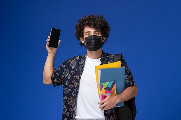 Vorderansicht junger männlicher student, der schwarze maske mit rucksack hält, der dateien und telefon auf dem blauen hintergrund hält.