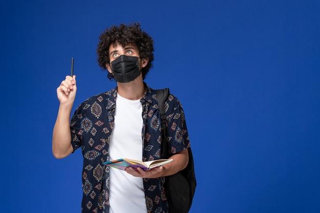 Vorderansicht junger männlicher student, der schwarze maske mit rucksack hält, der heft auf blauem hintergrund hält.