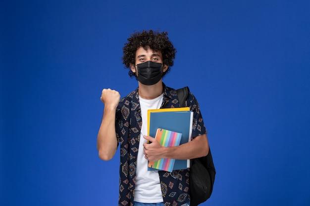 Vorderansicht junger männlicher student, der schwarze maske mit rucksack hält, der heft und dateien auf dem hellblauen hintergrund hält.