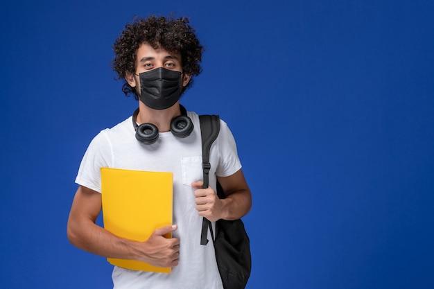 Vorderansicht junger männlicher student im weißen t-shirt, das schwarze maske trägt und gelbe dateien auf dem hellblauen hintergrund hält.