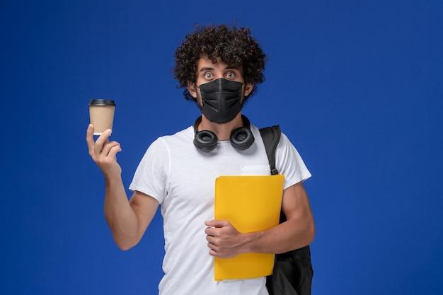 Vorderansicht junger männlicher student im weißen t-shirt, das schwarze maske trägt und gelben aktenkaffee auf blauem hintergrund hält.