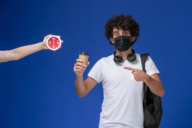 Vorderansicht junger männlicher student im weißen t-shirt, das schwarze maske trägt und kaffee auf dem blauen hintergrund hält.