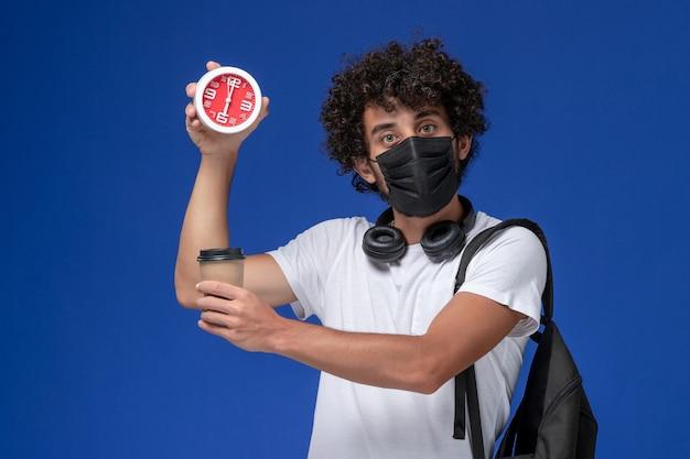 Vorderansicht junger männlicher student im weißen t-shirt, das schwarze maske trägt und kaffeetasse mit uhr auf blauem schreibtisch hält.
