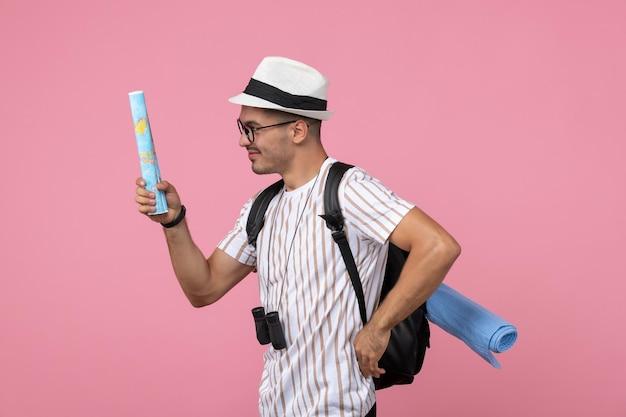 Vorderansicht junger männlicher tourist, der karten auf dem rosa hintergrund hält
