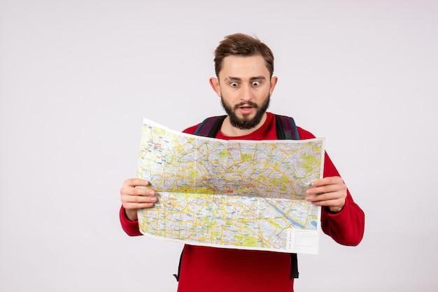 Vorderansicht junger männlicher tourist mit rucksack erkundungskarte auf weißer wand covid flugzeug urlaub emotion virus flugfarbe