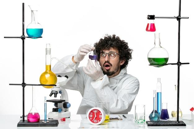 Vorderansicht junger männlicher wissenschaftler im speziellen anzug, der flasche mit lösung auf weißer wand hält
