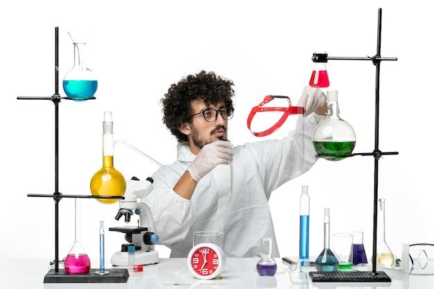 Vorderansicht junger männlicher wissenschaftler im weißen spezialanzug, der etwas auf weißem wandwissenschaftslabor hält, das männliche chemie bedeckt