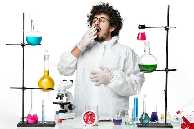 Vorderansicht junger männlicher wissenschaftler im weißen spezialanzug, der um tisch mit gähnenden lösungen steht