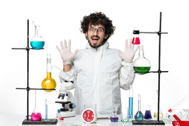 Vorderansicht junger männlicher wissenschaftler im weißen spezialanzug, der um tisch mit lösungen steht