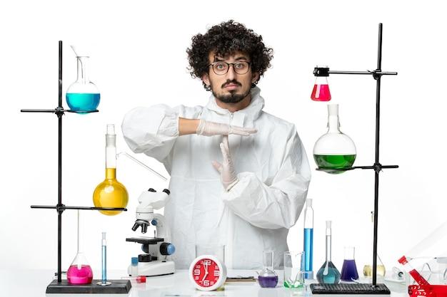 Vorderansicht junger männlicher wissenschaftler in weißem spezialanzug, der t zeichen auf weißer wand wissenschaft covid labor pandemie chemie zeigt
