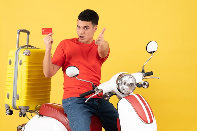 Vorderansicht junger mann auf moped hält kreditkarte, die fingerpistolengeste auf kamera zeigt