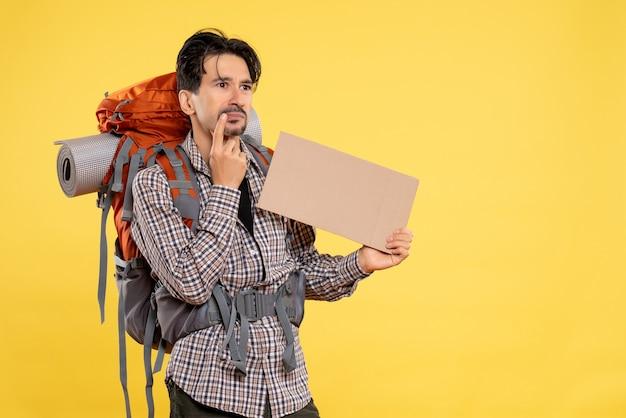 Vorderansicht junger mann beim wandern mit rucksack auf gelbem hintergrund farbe emotionen flugreise naturcampus