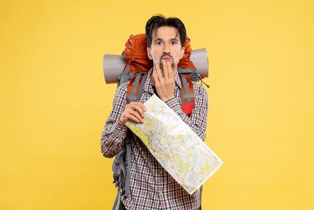 Vorderansicht junger mann beim wandern mit rucksack auf gelbem hintergrund verwirrt