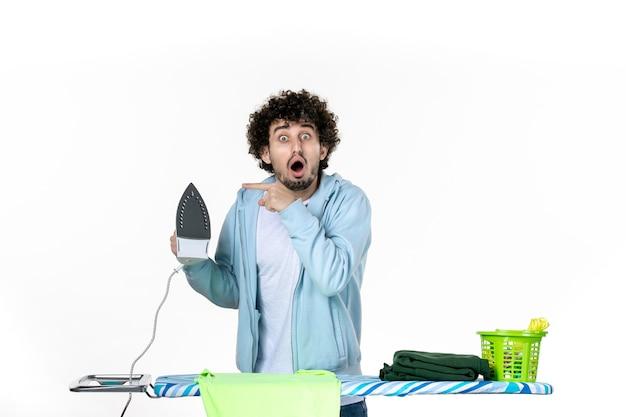 Vorderansicht junger mann bügeltuch an bord auf weißem hintergrund eisenfarbe mann wäsche foto kleidung hausarbeit reinigung