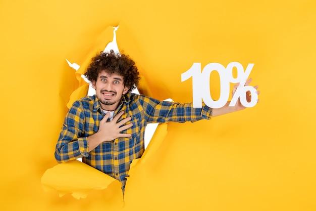 Vorderansicht junger mann, der auf gelbem hintergrund hält