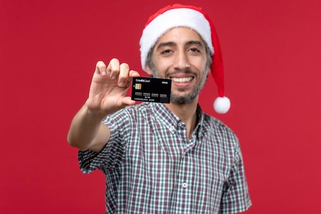 Vorderansicht junger mann, der bankkarte auf rotem hintergrund zeigt