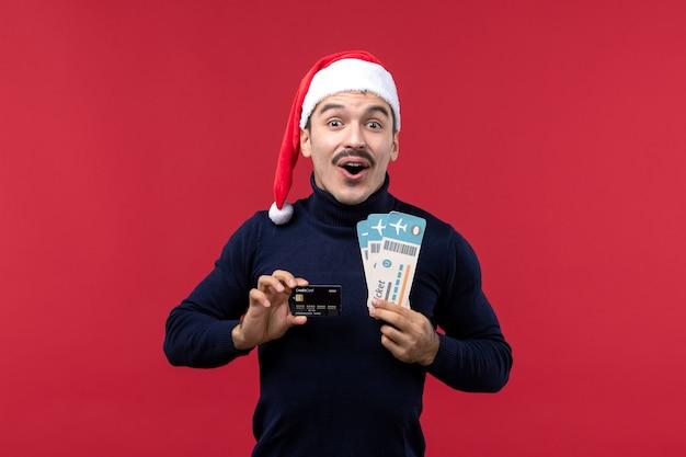 Vorderansicht junger mann, der bankkarte und tickets auf rotem hintergrund hält