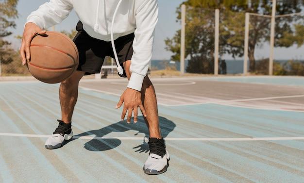 Vorderansicht junger mann, der basketball draußen spielt