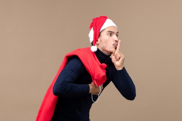 Vorderansicht junger mann, der bittet, auf braunem hintergrund weihnachtsferien santa ruhig zu sein
