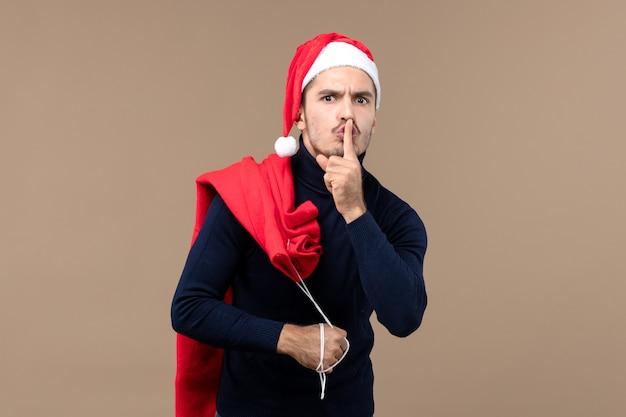 Vorderansicht junger mann, der bittet, auf braunem hintergrundweihnachtsferien-weihnachtsmann ruhig zu sein